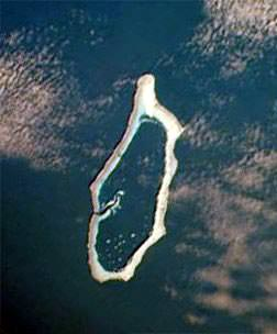 Hotsarahie from space. Photograph of a satellite image, shows the reef completely circles the deep lagoon with a single winding passage at the west. T